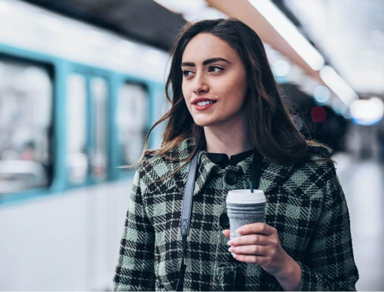 junge moderne Frau hält Kaffeebecher und lächelt