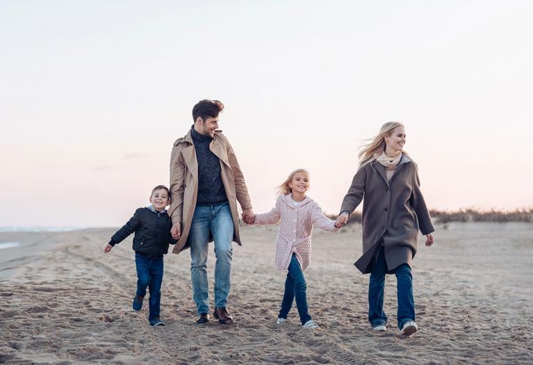 Junge Familie spaziert gut gelaunt am Strand