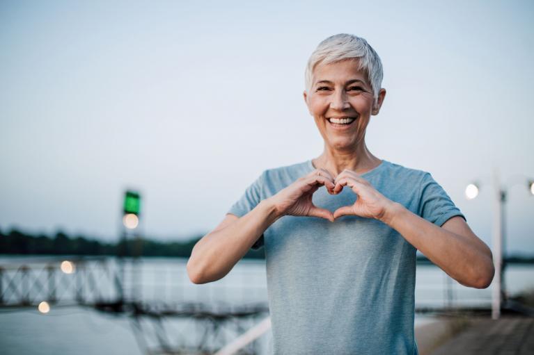 Ältere Frau zeigt Herz als Geste