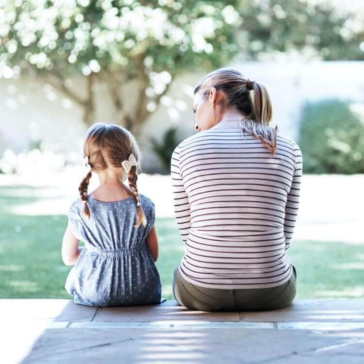 junge Frau sitzt neben Tochter von hinten