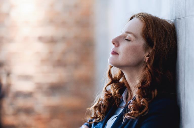 Frau lehnt sich an Wand mit geschlossenen Augen