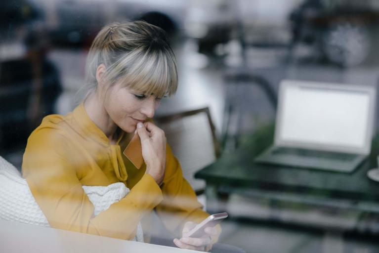 Frau schaut ins Handy im Sitzen