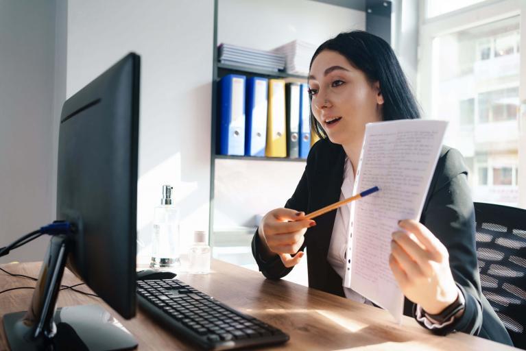 Junge Frau im Videochat mit einem Berater zu einer Krebsversicherung